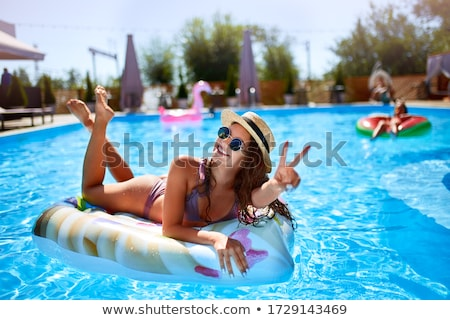 Woman sunbathing in bikini with straw hat Stock photo © RTimages