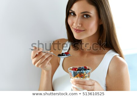 Close up of beautiful woman eating blackberries stock photo © dash