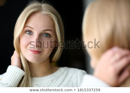 Portrait of the pretty young blonde near a mirror stock photo © acidgrey