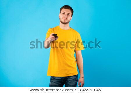 Portrait of a man switching of channel against a white background Stock photo © wavebreak_media
