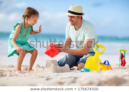 young family building sandcastle on beach holiday stock photo © monkey_business