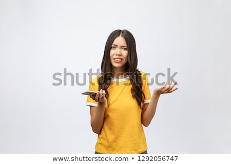 Young Asian woman talking on a mobile phone and looking confused Stock photo © bmonteny