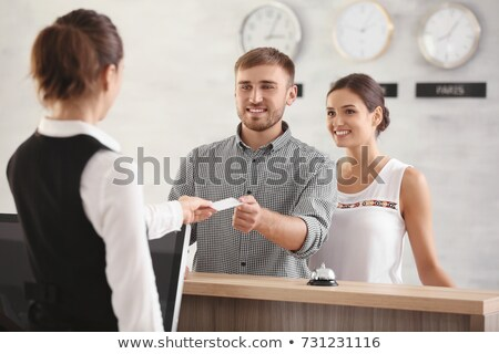 Receptionist - the hotel - give the young couple a room key Stock photo © Geribody