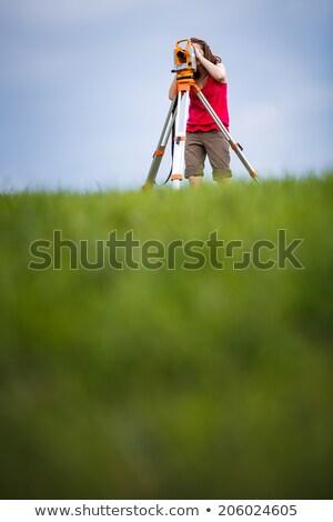 young female land surveyor at work   using the theodolite level stock photo © lightpoet