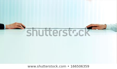 Closeup image of business hands holding two computer mouses with single cord Stock photo © deandrobot