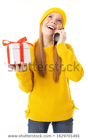 Beautiful redhead girl in christmas hat with telephone on yellow Stock photo © Massonforstock