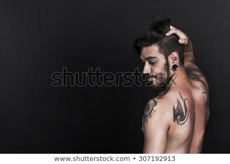 Man with pierced ear and tattoo. Stock photo © iofoto
