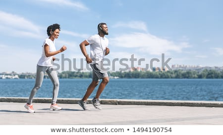 Young woman running in the city on river bank Stock photo © chesterf