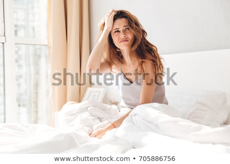 annoyed woman sitting in pajamas in bed stock photo © deandrobot