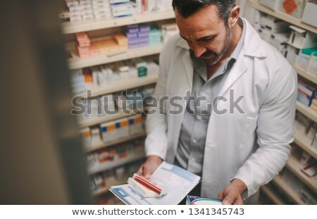 Stock photo: Pharmacist looking at pill box