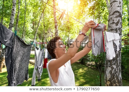 Woman hanging clothes on clothesline Stock photo © IS2
