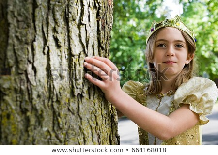 Girl dressed up as queen touching tree trunk Stock photo © IS2
