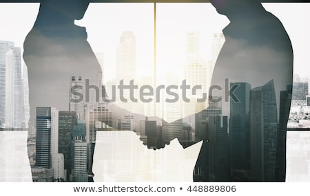 silhouette of young workers shaking hands in the office concept of teamwork and partnership double stock photo © alphaspirit