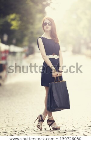 redhead happy woman walking outdoors holding shopping bags stock photo © deandrobot