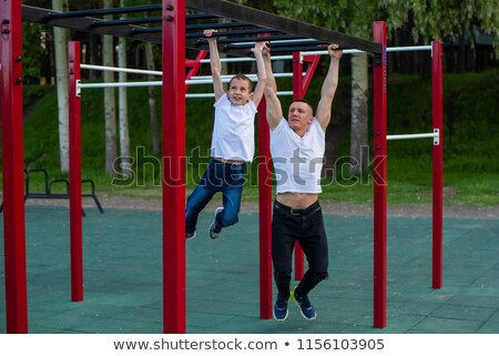 Father and son in the street gym in the park stock photo © galitskaya