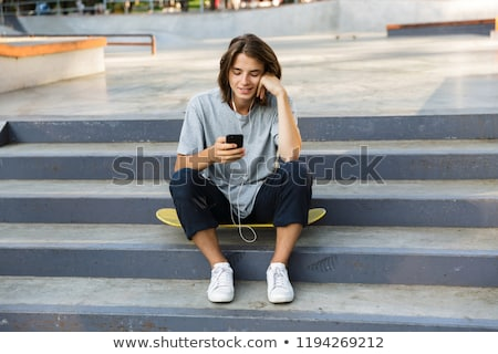 handsome happy oung skater guy sit in the park listening music with earphones using phone stock photo © deandrobot