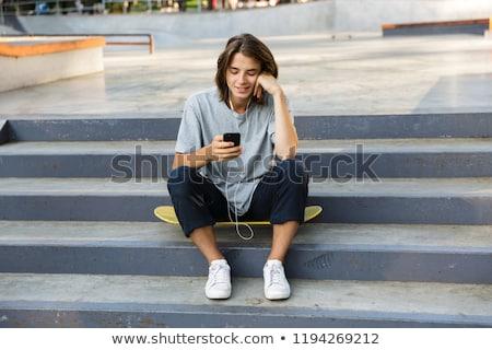 Jóképű boldog görkorcsolyázó fickó ül park Stock fotó © deandrobot