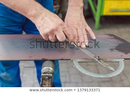 Metalworker with angle meter measuring strip of metal Stock photo © Kzenon