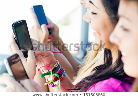 Happy three friends women using mobile phone. Stock photo © deandrobot