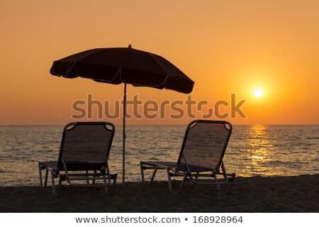 Hermosa playa cubierta sillas sombrilla amanecer Foto stock © Illia