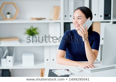 young manager in elegant dark blue dress consulting clients on the phone stock photo © pressmaster