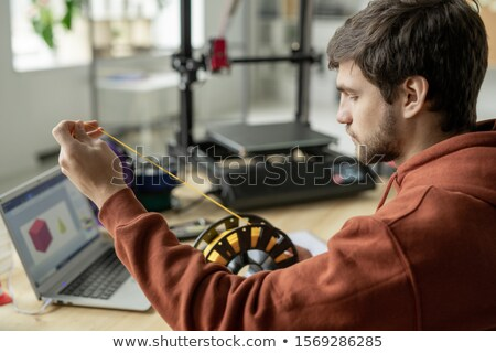 Young serious designer stretching yellow filament from spool to print 3d object Stock photo © pressmaster