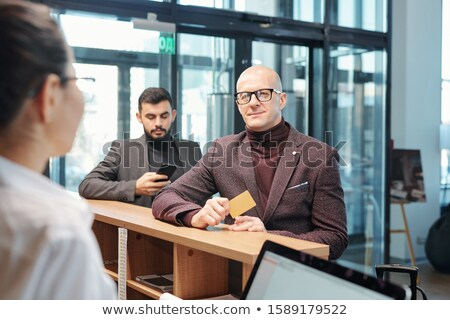 Bald mature business traveler with plastic card ordering room for night in hotel Stock photo © pressmaster