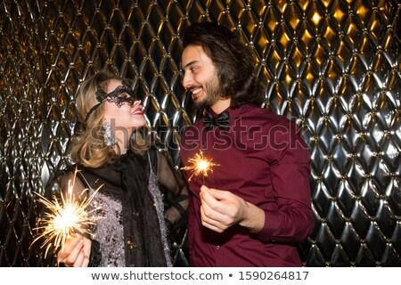 Smiling girl in venetian mask and her boyfriend holding sparkling bengal lights Stock photo © pressmaster