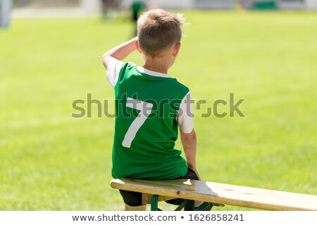 Soccer boy in grean jersey shirt sitting on wooden bench Stock photo © matimix