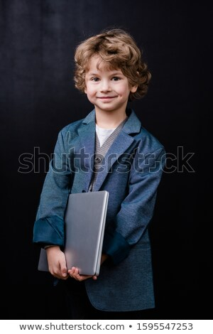Smiling little schoolboy holding folded laptop while standing in isolation Stock photo © pressmaster