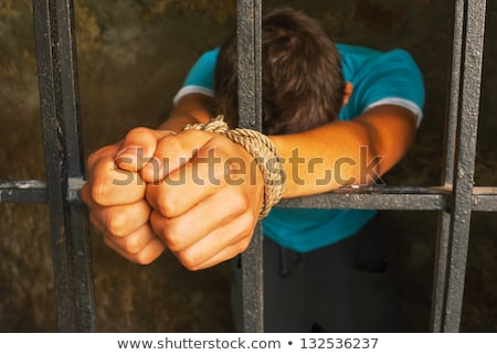 Stock photo: Man with hands tied with rope behind the bars
