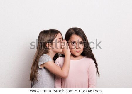 young beautiful girl whispering secret in her friends ear stock photo © stockyimages