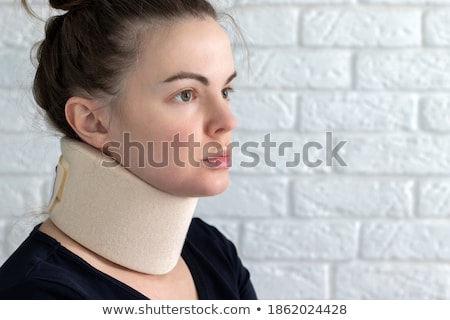 A young woman with a neck brace against white background Stock photo © wavebreak_media