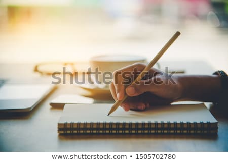 Pencil in hand writing on the notebook Stock photo © oly5