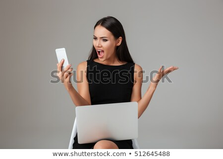 Beautiful woman in black dress sitting on the office chair over gray background Stock photo © deandrobot