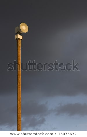 warning siren on a tall post against stormy sky Stock photo © PixelsAway