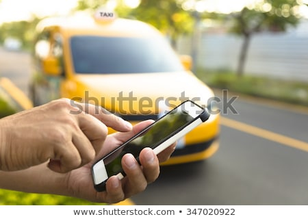 Taxi application. Man holds cell phone with taxi service app. stock photo © kali