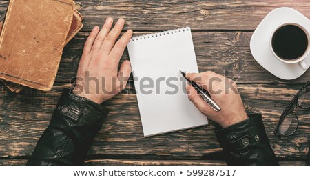 top view of man writing on paper on home office table Stock photo © LightFieldStudios