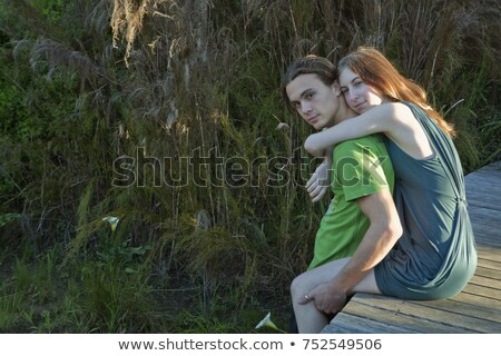 Girl on boardwalk with arms around man Stock photo © IS2