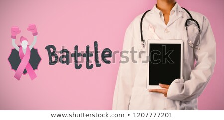 female doctor wearing breast cancer awareness pink ribbon holding a tablet Stock photo © wavebreak_media