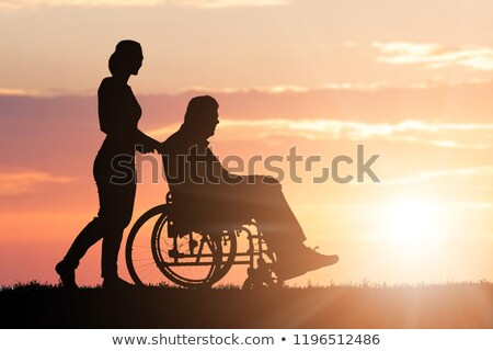 Silhouette Of Woman Assisting Her Disabled Father On Wheelchair Stock photo © AndreyPopov