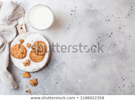 Stock photo: Healthy organic oat cookies with chocolate with glass of milk on wooden board on stone kitchen table
