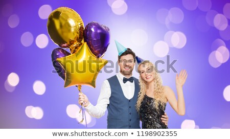 couple with party caps and balloons over lights Stock photo © dolgachov
