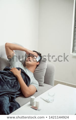 Sick young man suffering from flu at home Stock photo © Elnur