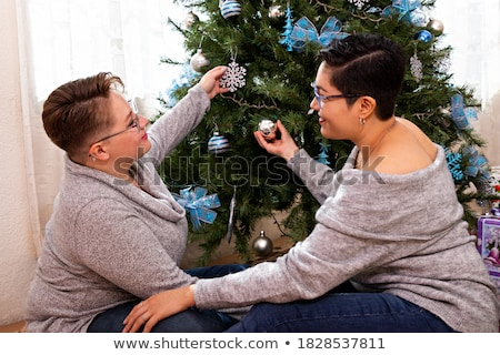 Young couple decorating fir tree for Christmas eve Stock photo © Kzenon