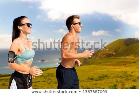 smiling couple running over big sur hills Stock photo © dolgachov