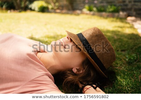 Top view of a joyful young girl in summer hat laying Stock photo © deandrobot