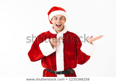 Image of kind man 30s in santa claus costume and red hat holding Stock photo © deandrobot