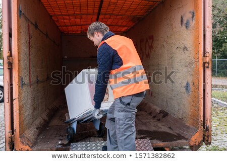 Man putting old washing machine in container Stock photo © Kzenon