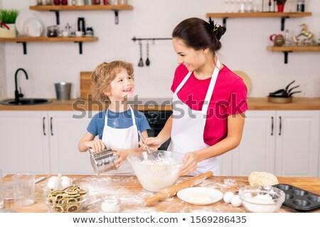 happy boy with sifter looking at his mother whisking eggs with flour in bowl stock photo © pressmaster